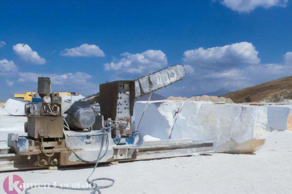 Mašina seče velike komade belog kamena.